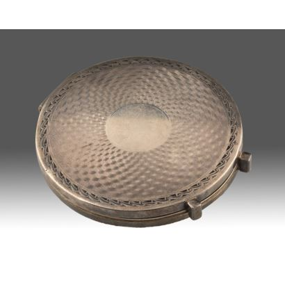 Elegante polvera circular de plata, con espejo en su interior. Peso: 82g. Diámetro: 8cm.