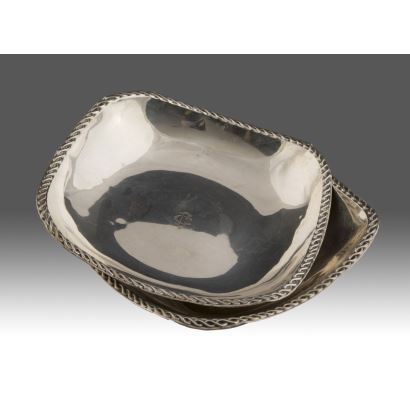 Elegante pareja de centro de mesa en plata, con  fino borde sogueado, iniciales grabadas en fondo. Marca de ley en borde. Peso: 273g. Ancho: 18cm.