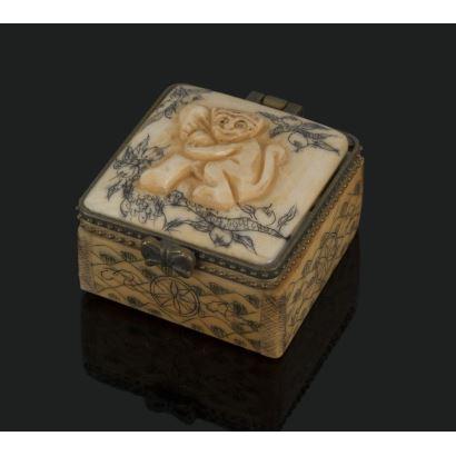 Cajita cuadrada tallada en hueso, representa en la tapa la figura de un mono. Medidas: 4x3,5x2,5cm.