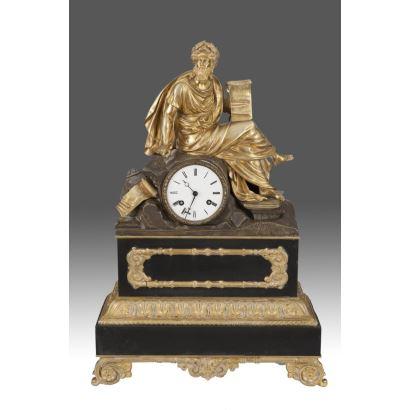Reloj de sobremesa francés del siglo XIX, en mármol y bronce dorado, decorado con figura de filósofo con cartela. Medidas: 60x39x15cm.