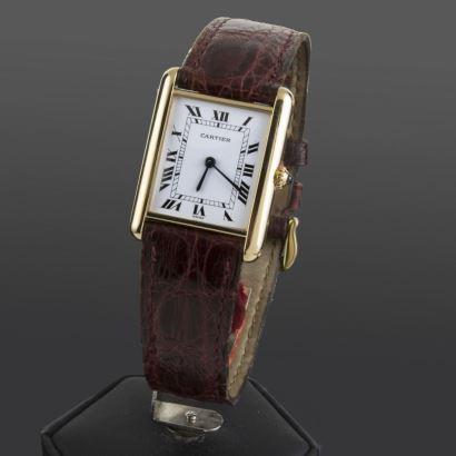 Reloj de pulsera CARTIER TANK, movimiento de cuarzo,  con caja de oro amarillo y pulsera de cuero.