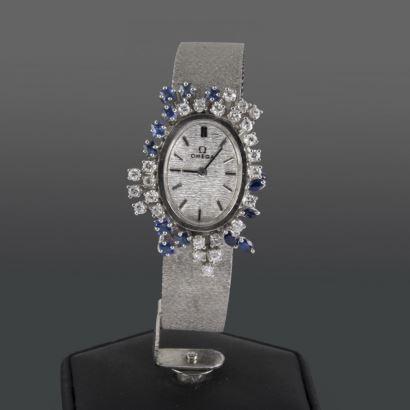 Reloj de pulsera para dama OMEGA VINTAGE, con elegante caja oval orlada por numerosos brillantes y zafiros.