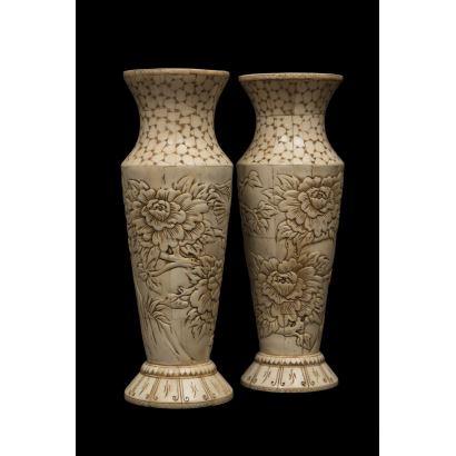 Pareja de jarrones chinos de hueso sobre base circular, ricamente decorados con motivos florales que cubren el cuerpo de la pieza en bajo relieve. Medidas: 25x10cm. Alto: 25cm.