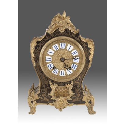 Magnífico reloj de sobremesa francés, en marquetería de Boulle, con decoración de rocalla en bronce dorado, se alza sobre cuatro patas. Siglo XIX. Medidas: 36x24x12cm.