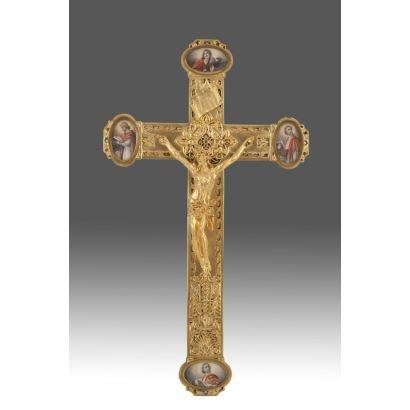 Importante cruz latina en bronce dorado al oro fino,  cuenta con la representación del Tetramorfos por medio de placas ovales en marfil  rematando los brazos, cada una con un Evangelista. Siglo XIX. Medidas: 37x21,5cm.