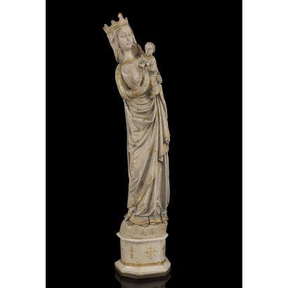 Excepcional talla neogótica de principios del siglo XX,  representa a la Virgen con el Niño sujetando una flor, detallismo en túnicas, se alza sobre peana del mismo material,  presenta detalles en dorado. Medidas: 77,5x16x15cm.