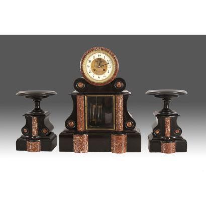 Magnífico reloj de sobremesa francés con guarnición de peanas y péndulo de mercurio, firmado PAVARD-FAISIANT / VILLENEUVE D'INGRE. En mármol negro que alterna con mármol rojo jaspeado. Siglo XIX. Reloj: 52x18x44cm. Peanas: 25x18x18cm.