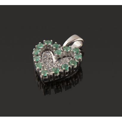 Llamativo colgante  de oro blanco 18K en forma de corazón decorado con 10 diamantes  y 14 esmeraldas. Peso: 1,86 gr.