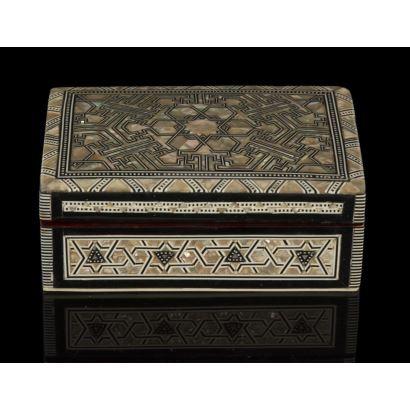 Cajita con estructura de madera con forma rectangular, está decorada con taracea de nácar, ébano y hueso que forman motivos coptos, árabes y judíos, con interior forrado en terciopelo. 14x9cm.