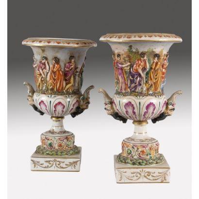 Bella pareja de cráteras de porcelana de Capodimonte. Relive de friso corrido con personajes clásicos. ss.XIX-XX. 35x20cm