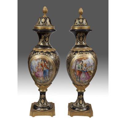 Elegante pareja de jarrones, realizados en porcelana tipo SÈVRES, s.XX, decorados con bonitas escenas bucólicas sobre fondo azul cobalto con detalles en dorado. Alto: 58cm.