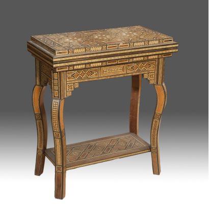 Excepcional mesa de juego realizada en marquetería formando diseños geométricos, presenta tablero desplegable para backgammon y ajedrez, con bonitas patas curvas unidas por chambrana. Medidas cerrada: 64x32x72,5cm. Abierta: 64x64,5cm.
