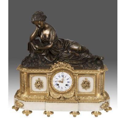 Elegante reloj de sobremesa en mármol y bronce, rica base con apliques en bronce dorado y cuerpo superior en bronce patinado con imagen de joven muchacha leyendo. Siglo XIX. Medidas: 57x55x16cm.