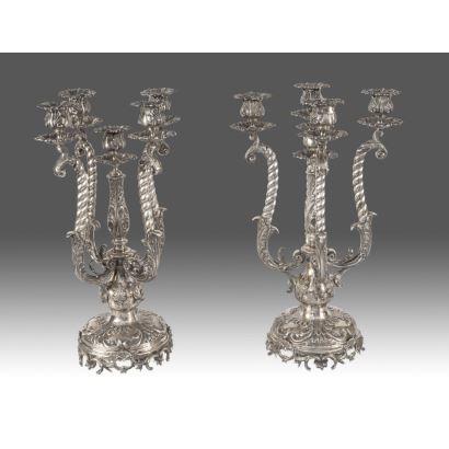 Importante pareja de candelabros de cinco luces de  mesa, con pie circular y brazos en espiral, en plata 900, con elegante decoración de rocalla y venera. Marca de ley en base. Peso: 7800g. Medidas: 50x22cm.