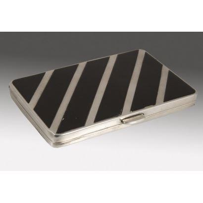 Bella cajita rectangular rectangular realizada en plata, cuenta con una elegante decoración de franjas negras que se alternan con el metal. Marcas en borde interior. 8x5,5cm.
