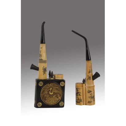 Magnífica pareja de pipas orientales realizadas en hueso y madera ebonizada, con rica decoración tallada. s.XIX. Leve desperfecto. Medidas: 23x8x4cm y 21x7x2,5cm.