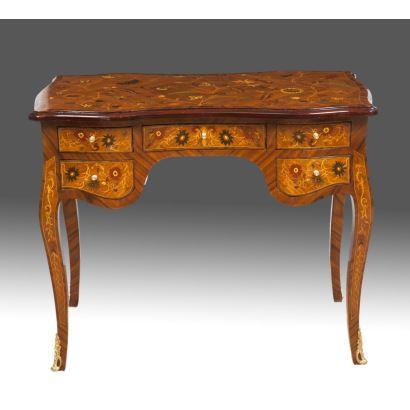 Elegante escritorio en madera con ricos motivos florales en marquetería, cuenta con cinco cajones y cuatro estilizadas patas cabriolé con pie en bronce dorado. Medidas: 80x100x55cm.