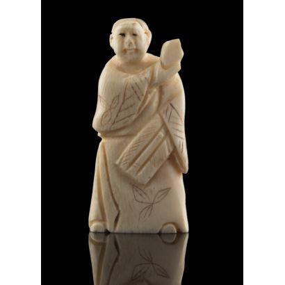 Netsuke en marfil de hipopótamo, se trata de un personaje con kimono sujetando un objeto circular. Medidas: 5x2,5cm.