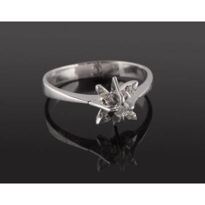 Elegante anillo de oro blanco 18K con diamante central talla brillante de 0,08 quilates, rodeado de otros 4 diamantes. Total: 0,14 quilates. Peso:  4,22 gr.