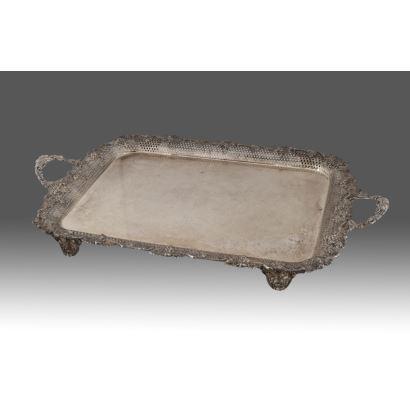 Magnífica bandeja plateada con cuatro patas y doble asa, decorada con rocalla y vid, detalles calados. Medidas: 57x43x4,5cm.