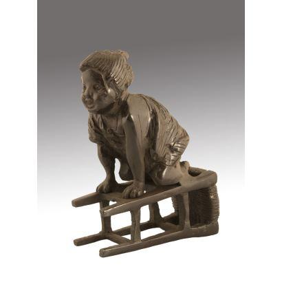 Figura de bronce en la que vemos a una niña sonriente jugando sobre un taburete tumbado. Medidas: 12,5x9x4,5cm.