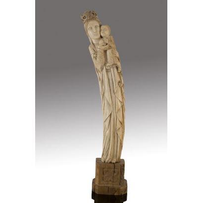 Importante talla del siglo XIX realizada en marfil sobre peana de madera, representa a la Virgen coronada sujetando al Niño en brazos. Alto: 75cm. Con peana:87cm.