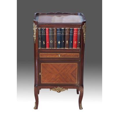 Mueble auxiliar en madera, la pieza se apoya sobre cuatro patas cabriolé y cuenta con dos puertas y un cajón, una de las puertas presenta forma de falso librero. Medidas: 65x30x40cm.