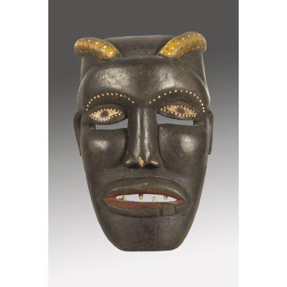 Máscara  africana realizada en madera tallada y policromada, representa a un personaje con la boca abierta y cornamenta. 39x25cm.
