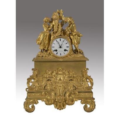 Excepcional reloj de sobremesa en bronce dorado al oro fino,  rematado con escena galante y rica decoración de rocalla en base. Francia s.XIX.  Firma en esfera: C.DETOUCHE Ft. 158&160 Rue St Martin. Medidas: 44x30cm.