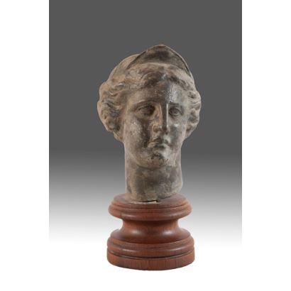 Figura antigua en bronce sobre peana de madera.