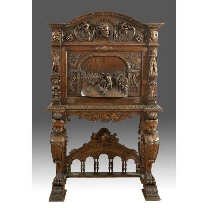 Excepcional escritorio a muestra cubierta tallado en madera, se alza sobre pie de puente, la tapa presenta escena Bíblica  de Cristo atado a la columna. Medidas:  175x108x50cm.