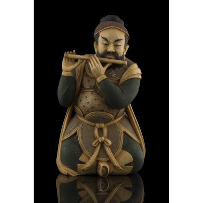Importante talla de marfil policromada, se trata  de un personaje masculino dotado de gran realismo sentado tocando una flauta. Sello en base. Con certificado de antigüedad de la Federación Española de Anticuarios. Altura: 15,5cm.