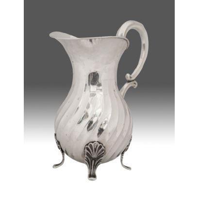 Elegante jarra de plata punzonada, se alza sobre tres pequeñas patas y cuenta con asa, presenta decoración estriada. Medidas: 24x22cm. Peso: 682g.