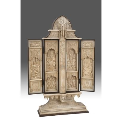 Tríptico neogótico en marfil sobre estructura de madera, a modo de parteluz se encuentra la imagen de la Virgen con el Niño, a sus lados diversos registros con escenas bélicas medievales bajo arcos, corona la pieza la cruz de la Orden de Malta. Con CITES.