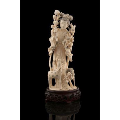 Magnífica figura en marfil sobre peana de madera, en ella contemplamos a una geisha sujetando flores, a sus pies un ciervo y un ave. Con certificado de antigüedad. Marca en base. Alto sin peana: 24cm.