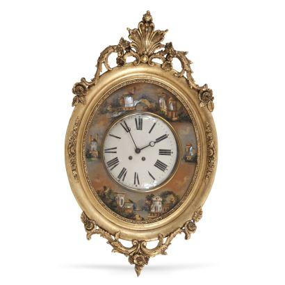 Reloj de pared isabelino, S. XIX. Realizado en madera tallada, dorada, policromada con aplicaciones de nácar. Con péndulo y llave. Medidas: 105 x 63 cm.