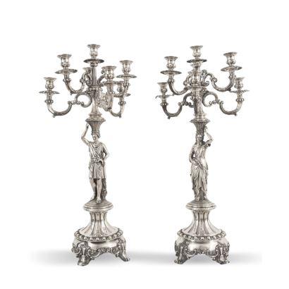 Pareja de candelabros en plata, c. 1900. De siete luces. Presenta dos figuras alegóricas de un segador y una figura femenina con una corona de flores. Altura: 67 cm. Peso: 4.167 g.