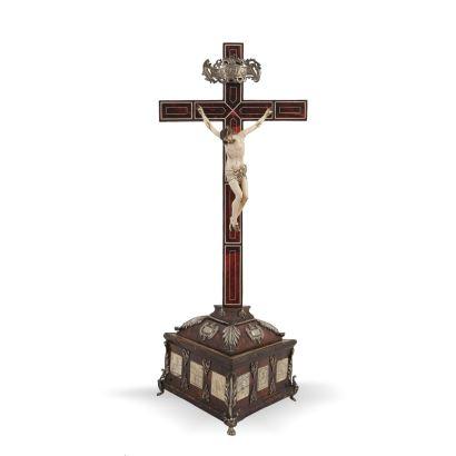 Cruz de altar, S. XVII y posterior. Presenta Cristo realizado en marfil con peana con carey y hueso. Peana trapezoidal con escenas grabadas sobre hueso y aplicaciones de plata y carey. Medidas: 82 cm x 33 x 33 cm.