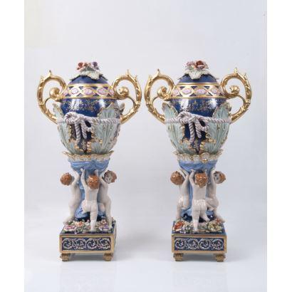 Destacada pareja de jarrones en porcelana policromada, esmaltada y dorada, con base cuadrada y astil formado por niños que sostienen en alto un huevo con tapa y asas de roleo sobre fondo azul. Marca en base. Medidas: 64x24x34cm.