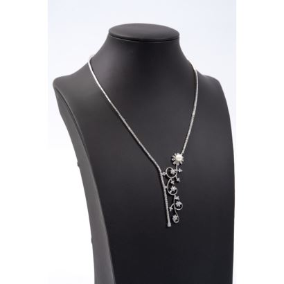 Elegante gargantilla articulada en oro blanco, con decoración de roleos y flores de brillantes en carril, con una perla. Brillantes:  1,68cts aprox; peso:  28,8g; longitud: 44cm.