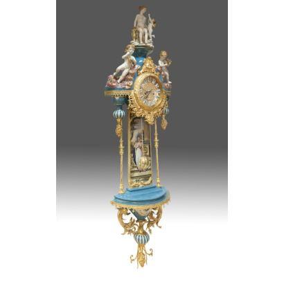Gran reloj de pared con péndulo, en porcelana policromada y bronce dorado, rematado por figura de Venus y Cupido. Medidas: 170x50cm.