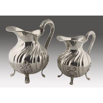 Pareja de jarras realizadas en plata de ley, ambas se alzan sobre elegantas patas de roleo y presentan decoración gallonada. 23x20cm. 16x17cm. Peso total:1100g.
