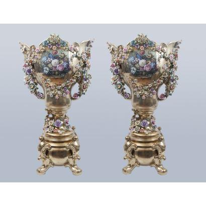 Gran pareja de jarrones en porcelana dorada y policromada, con decoración de bodegón floral en medallón y flores en relieve de varios colores. Medidas. 114x66x41cm.