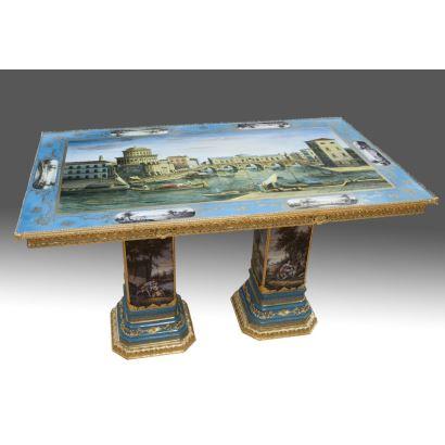 Mesa con tablero rectangular realizada en porcelana policromada, se alza sobre doble pie de pedestal, cuenta con decoración arquitectónica en tablero y escenas galantes en patas, con apliques en bronce dorado. Medidas: 90x151x89cm.