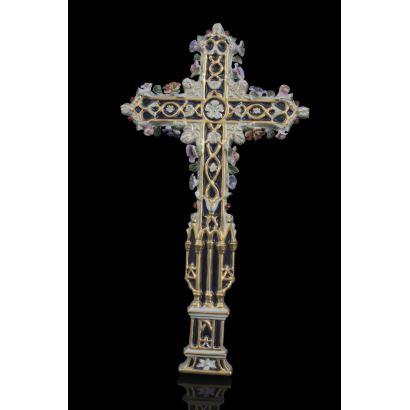 Bonita cruz de porcelana para colgar, está ricamente decorada con motivos florales y brazos en azul con detalles dorados. Medidas: 37x20cm.