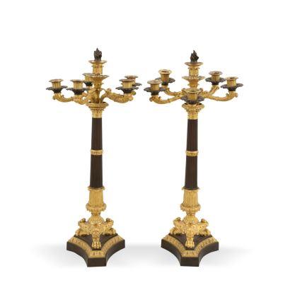 Pareja de candelabros Carlos X, S. XIX. Realizados en bronce pavonado y dorado. Presentan 6 luces, fuste acanalado sobre pie trípode y patas de garra. Decoración vegetal con palmetas y roleos.  Altura: 65 cm.