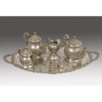 Magnífico juego de café/té en plata repujada con motivos vegetales entre roleos y molduras. Cuenta de doce tazas, dos jarras, azucarero, pinzas, lechera, colador y bandeja. Marcas de punzón de platero en base. 8925g