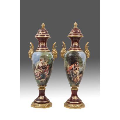 Bella pareja de jarrones con tapa en porcelana policromada con escenas galantes y de paisaje en parte central, sobre fondo granate, con pie y asas de carnero en bronce dorado. Alto: 57cm.