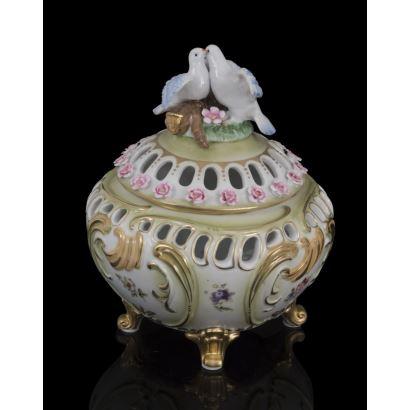 Bellísima bombonera en porcelana policromada donde encontramos decoración en relieve formando rocallas doradas, rematada por dos palomas en la tapa. 22,5x18,5cm.
