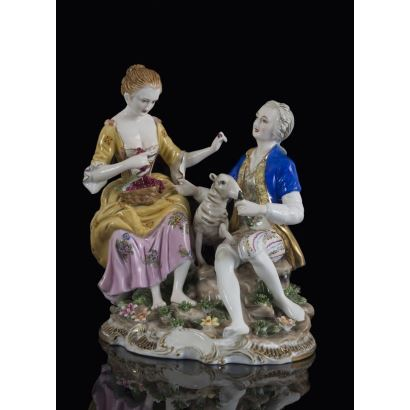 Figura en porcelana policromada de gusto bucólico, en ella un hombre y una mujer comen una uvas, entre ellos una oveja. Marca en base. 27x25x20cm.
